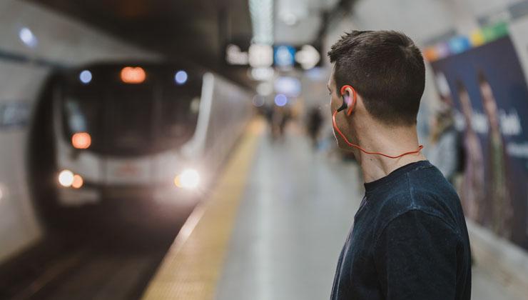通勤時間にオーディオブックを聴く男性