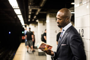 電車を待ちながら読書する男性