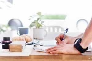 テーブルの上でノートを取る男性