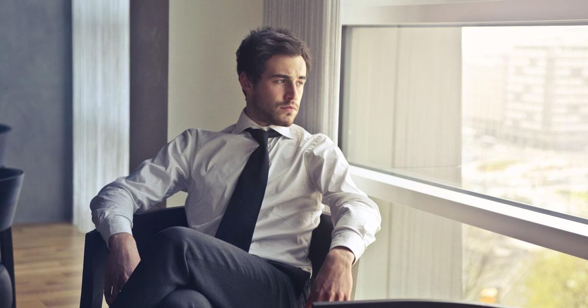 窓の外を物思いに耽ながら眺める男性